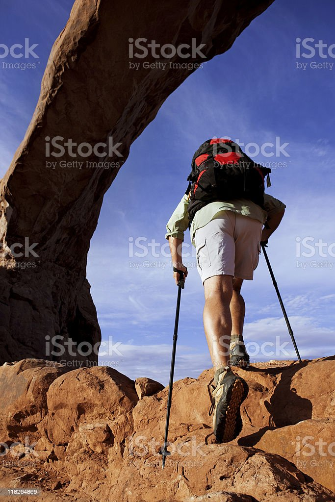 Male Hiker With Climbing Poles Hiking Up Steep Rocks royalty-free stock photo