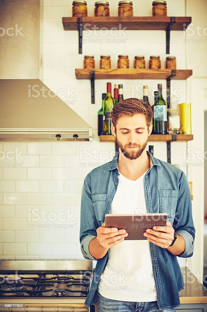 Male hipster using tablet computer in kitchen stock photo