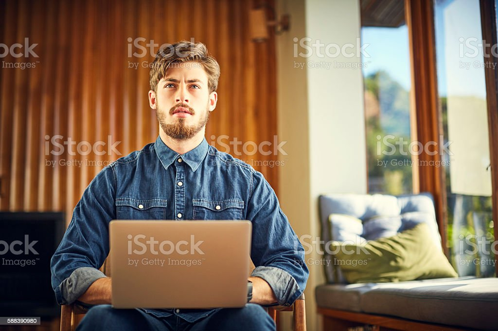 Male hipster with laptop looking away working at home stock photo