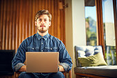 Male hipster with laptop looking away working at home