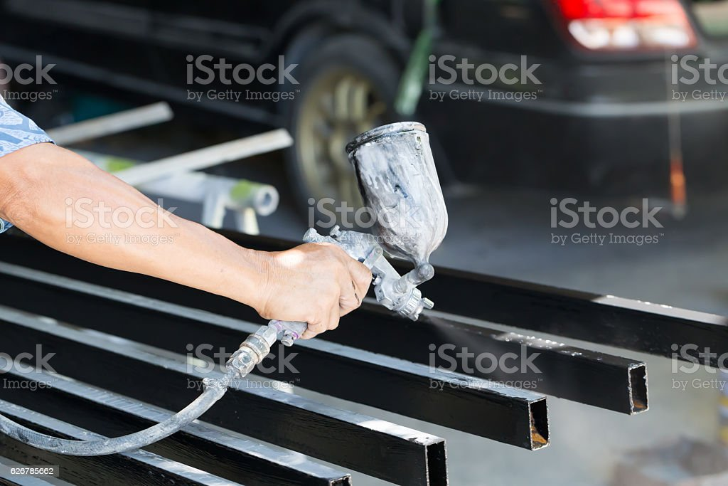 Male holding spray gun and painted steel stock photo