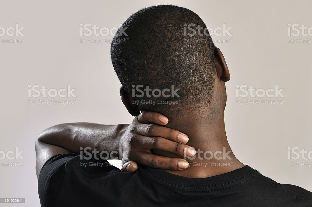 Male holding the back of his neck cause of pain stock photo