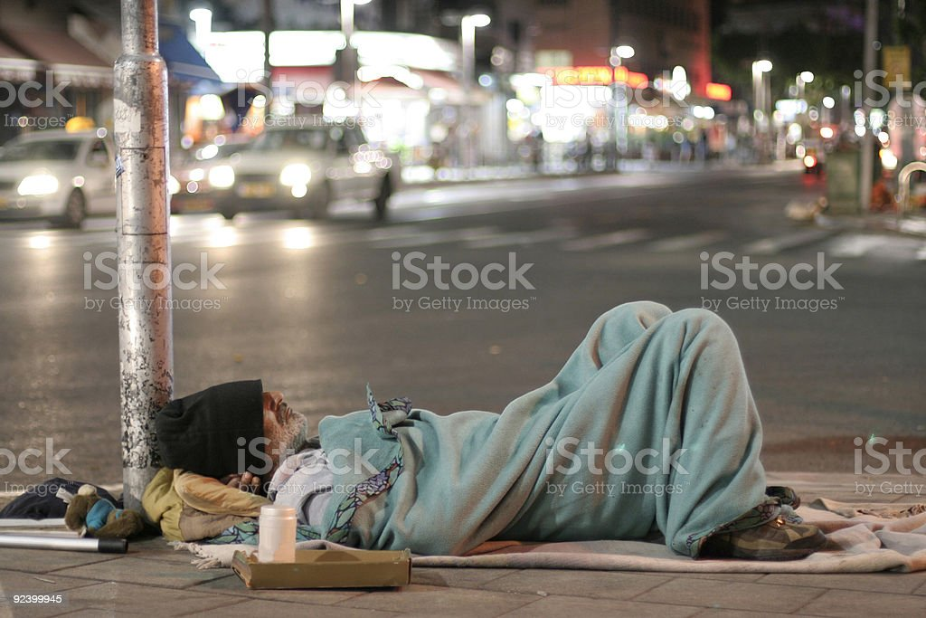 male homeless sleeping in a street stock photo
