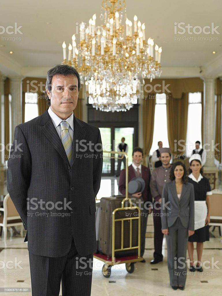 Male hotel manager standing in foyer, staff in background, portrait royalty-free stock photo