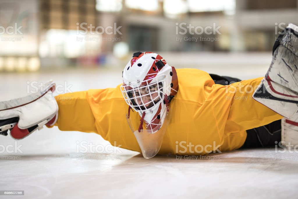 Male ice hockey goaltender having fun while lying on ice in a rink. stock photo