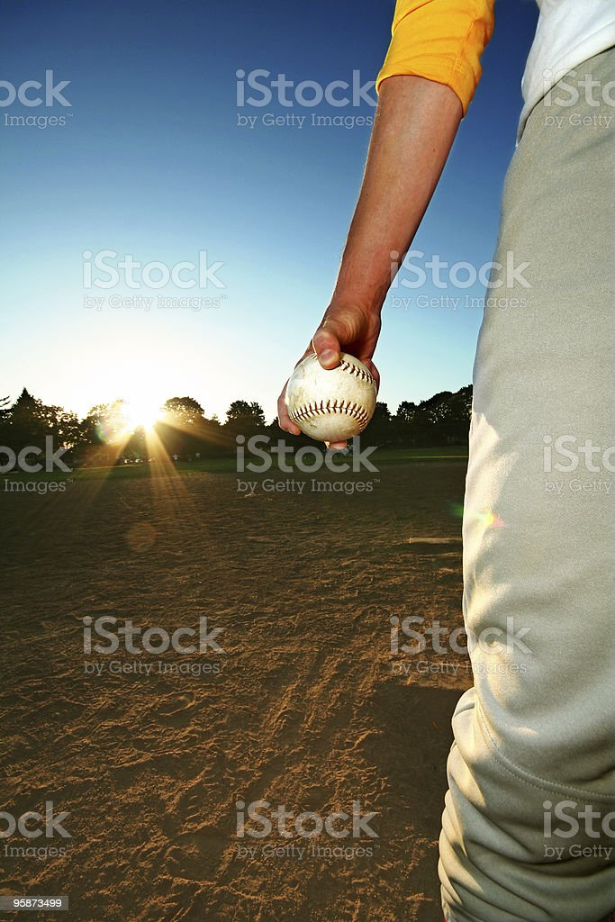 Male in Baseball Uniform Holding a Baseball at Sunset stock photo