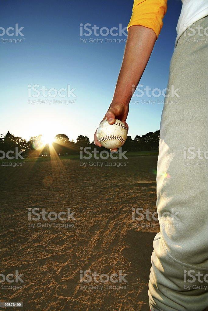 Male in Baseball Uniform Holding a Baseball at Sunset stock photo
