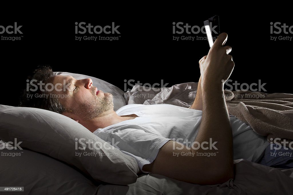 Male in Bed Browsing the Internet with a Tablet stock photo