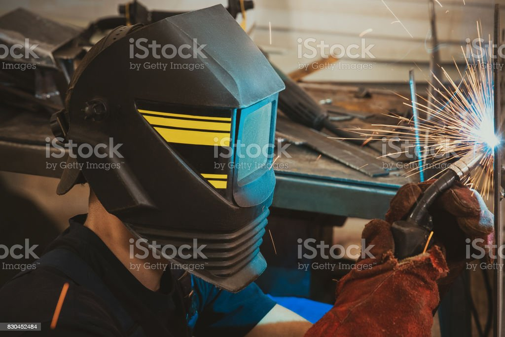 Male in face mask welds with argon-arc welding stock photo