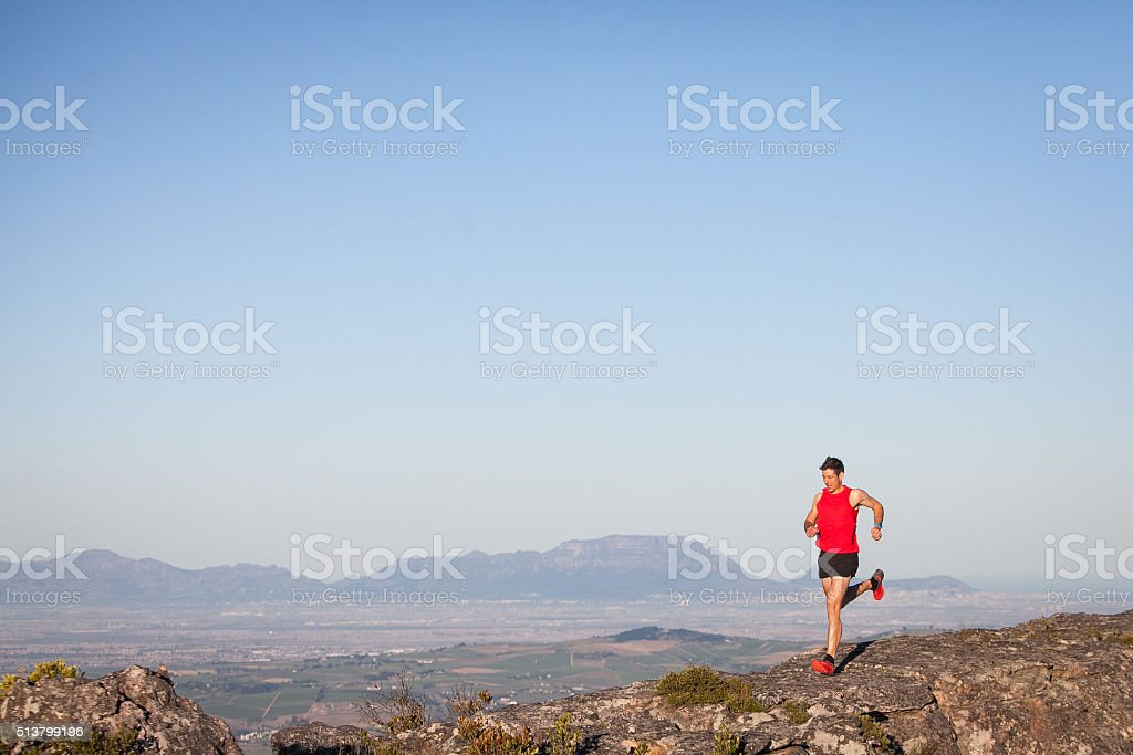 Male in red out running on the mountain stock photo