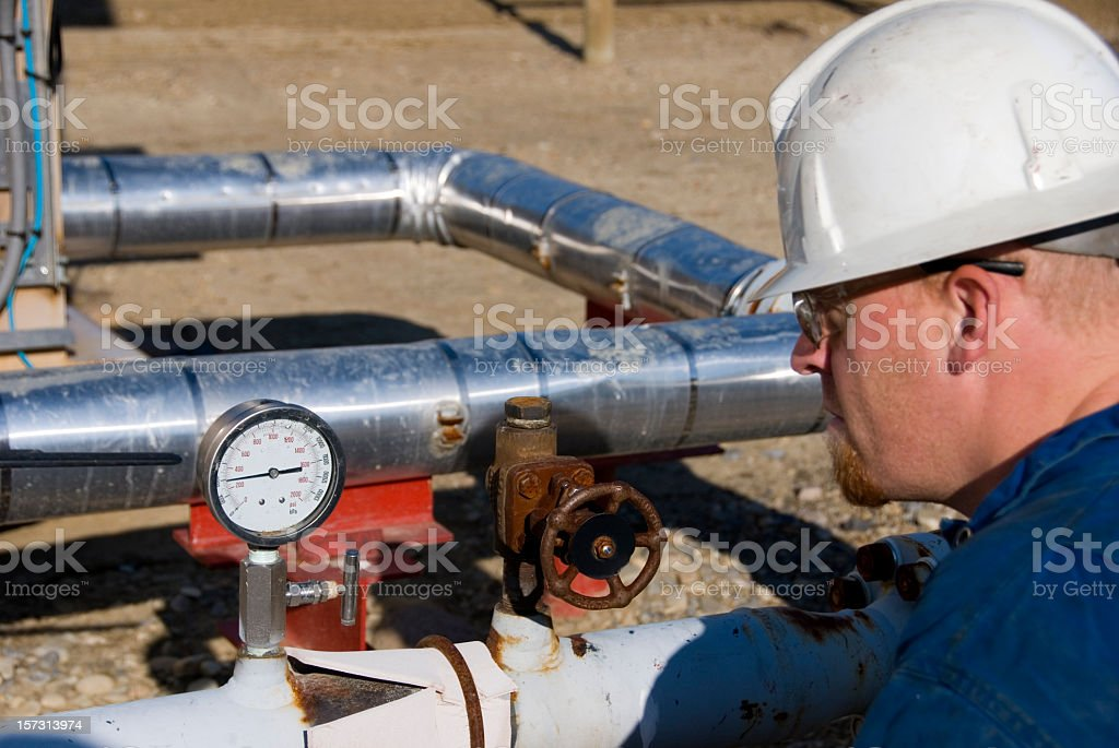 A male industrial worker and a set of pipes with a gauge stock photo