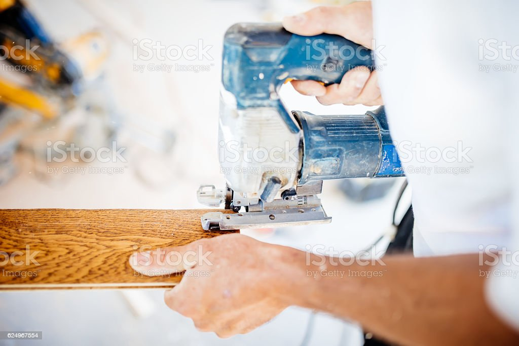 male industrial worker builder working with electric jigsaw and wood stock photo
