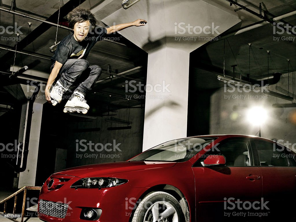 Male inline skater jumping over car stock photo
