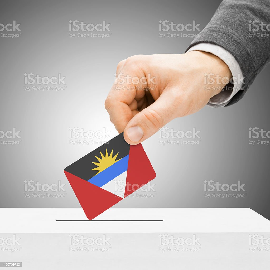 Male inserting flag into ballot box - Antigua a stock photo