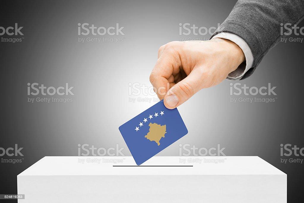 Male inserting flag into ballot box - Kosovo stock photo