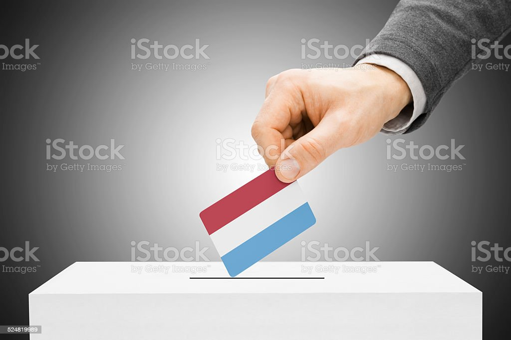 Male inserting flag into ballot box - Luxembourg stock photo