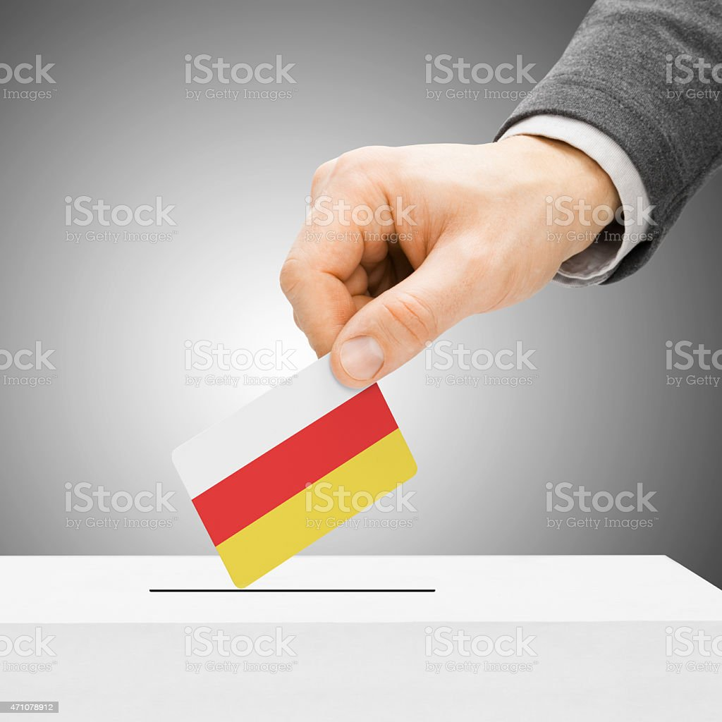 Male inserting flag into ballot box - South Ossetia stock photo