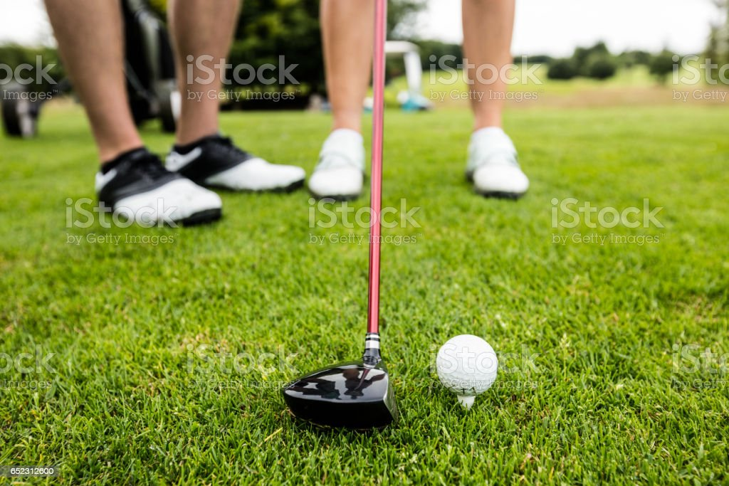 Male instructor assisting woman in learning golf stock photo