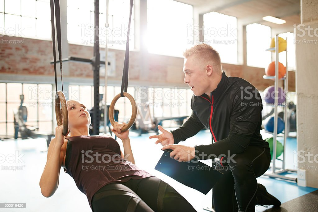 Male instructor helping a woman during workout stock photo