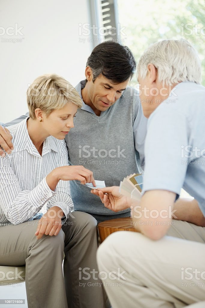 Male interior designer showing textile swatches to a couple royalty-free stock photo
