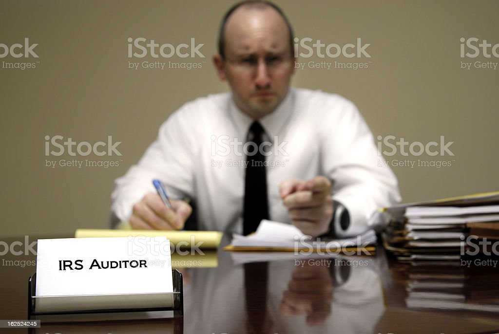 A male IRS tax auditor at a desk with paperwork stock photo