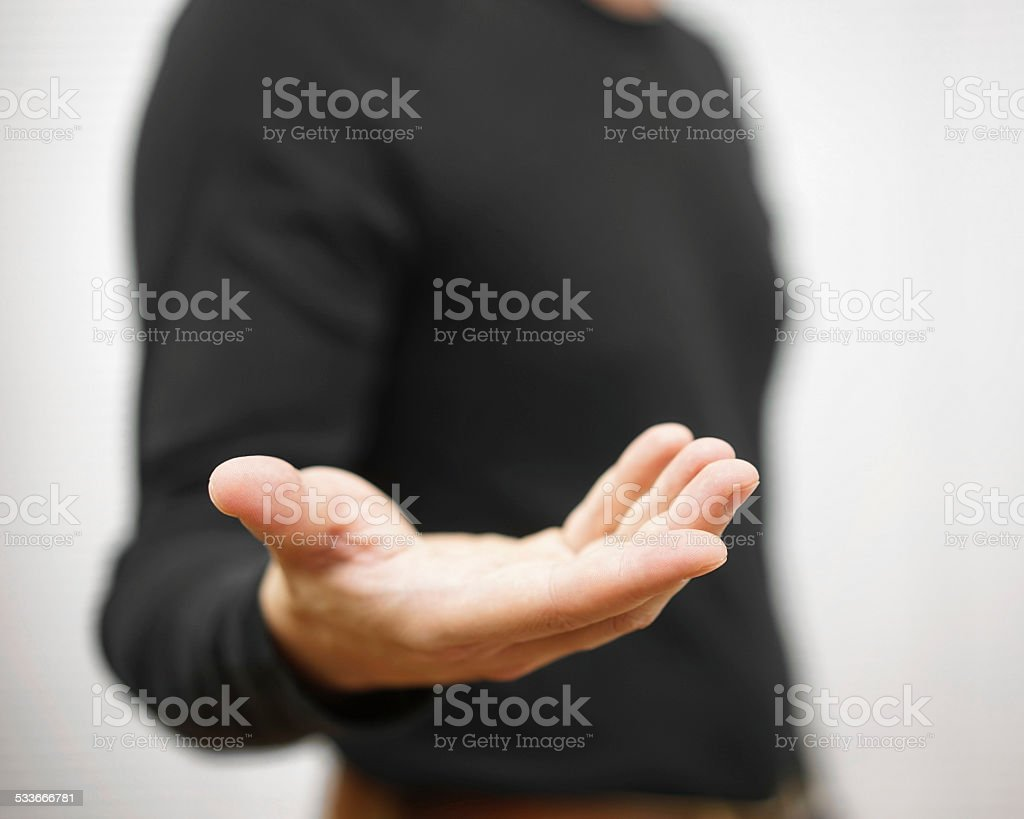 male is standing  and shows outstretched hand with open palm stock photo