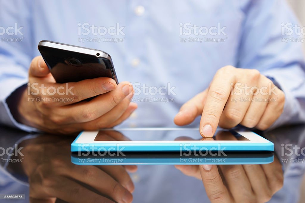 male is using smart mobile phone and tablet computer stock photo