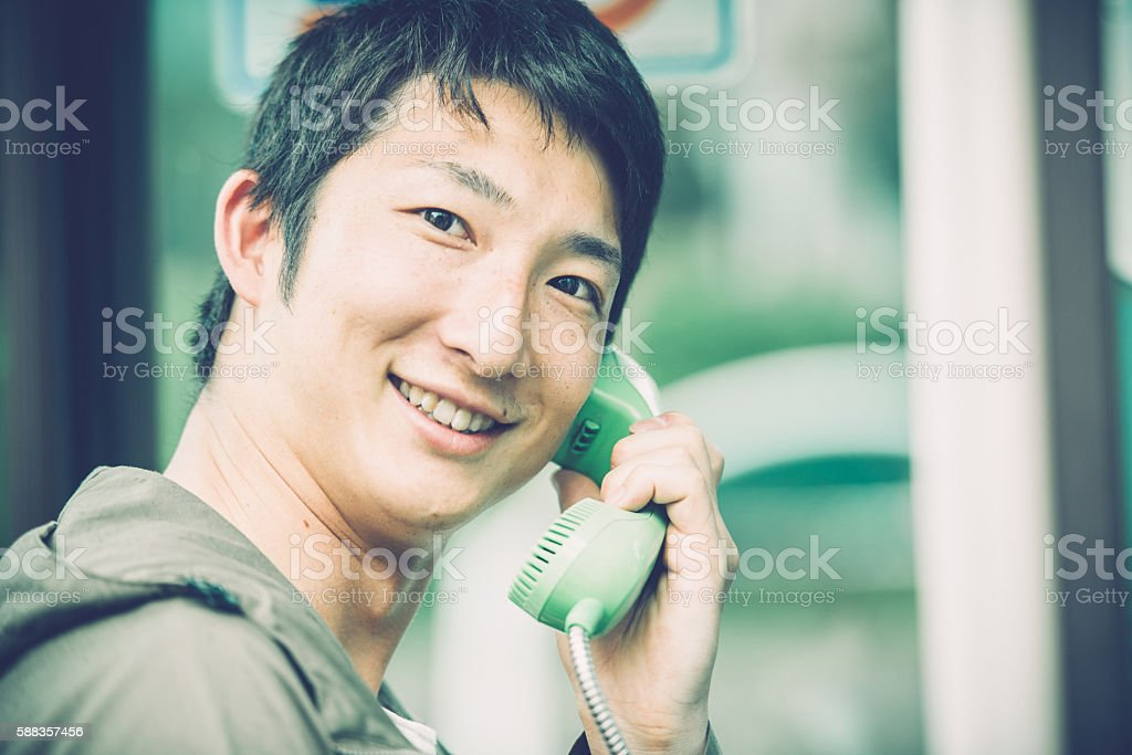 Male Japanese Student in Telephone Box, Kyoto, Japan, Asia stock photo