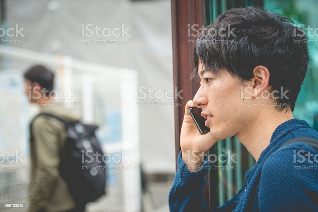 Male Japanese Student Using Smart Phone, Kyoto, Japan, Asia stock photo