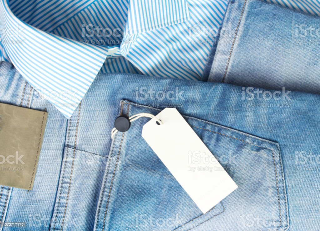 Male jeans shirt white tag.Men's fashion clothes background. stock photo