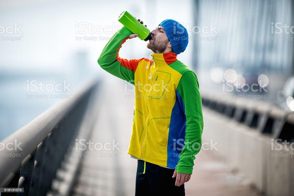 Male jogger resting on the bridge stock photo