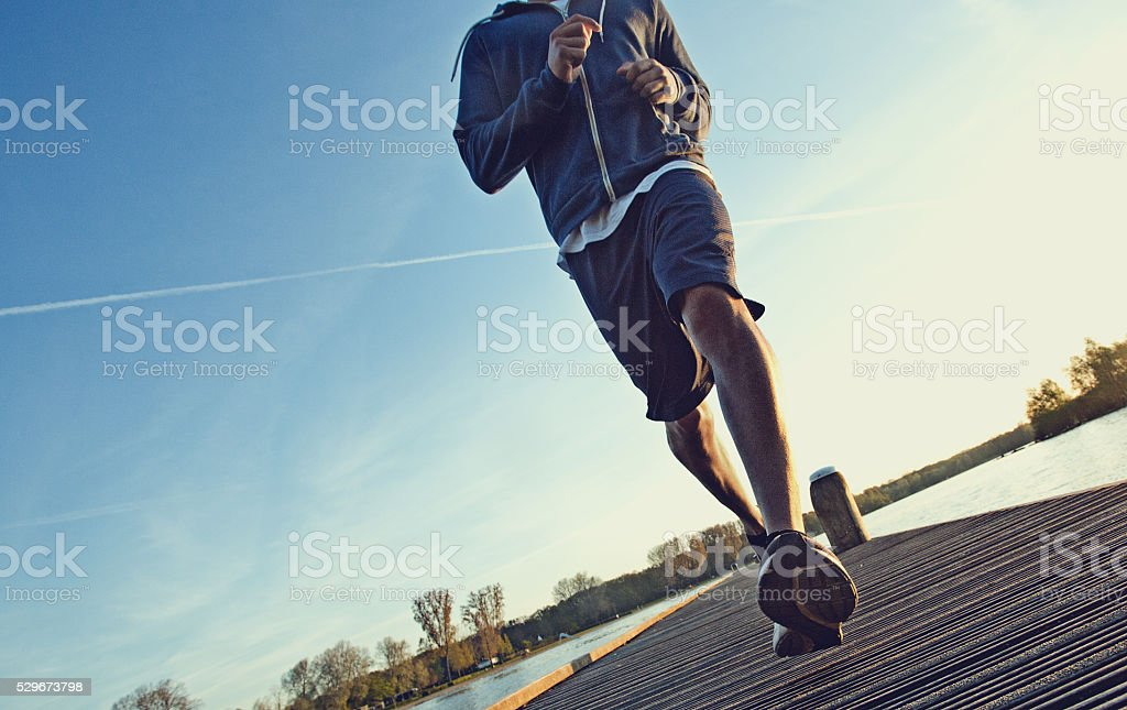 Male jogging at dawn on a lakeside pier stock photo