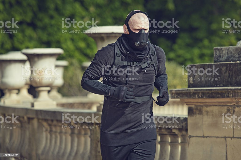 Male jogging in black in Paris park wearing breathing apparatus stock photo