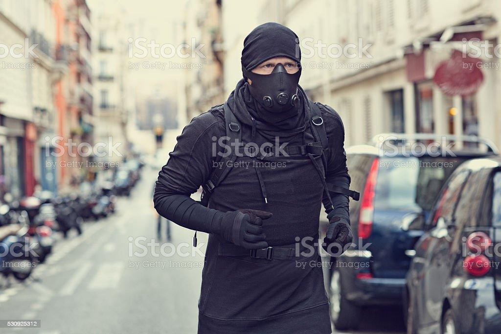 Male jogging in black in Paris street wearing breathing apparatus stock photo