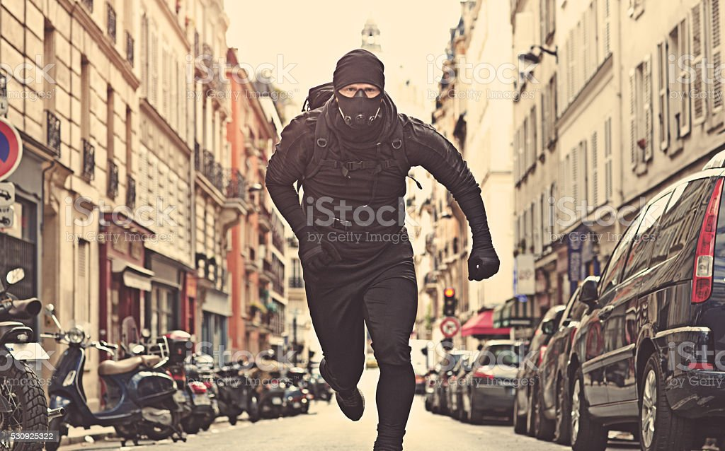 Male jogging in black in Paris street wearing breathing apparatus stock photo