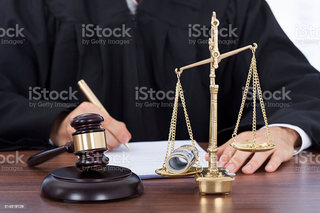 Male Judge Signing Document In Courtroom stock photo