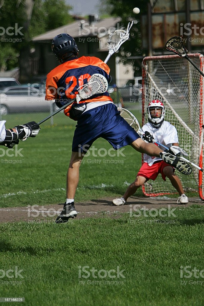 Male Lacrosse Player Flings High-flying Shot on Goal royalty-free stock photo