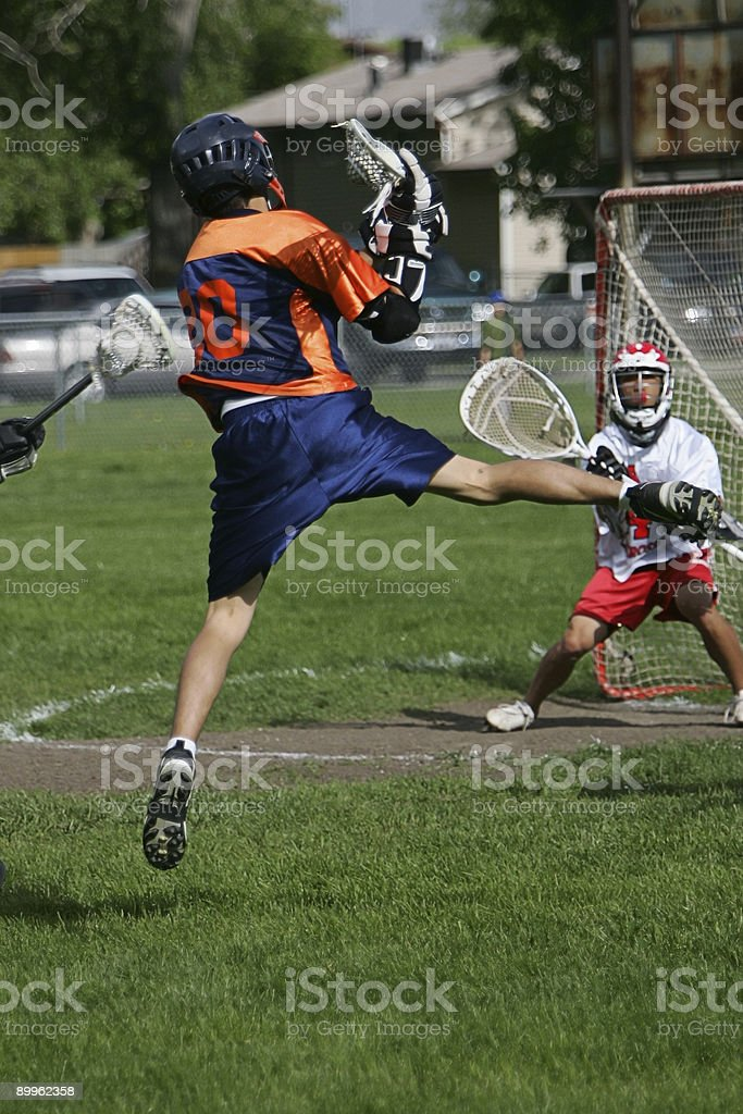 Male Lacrosse Player Jumps High for Shot on Goal royalty-free stock photo