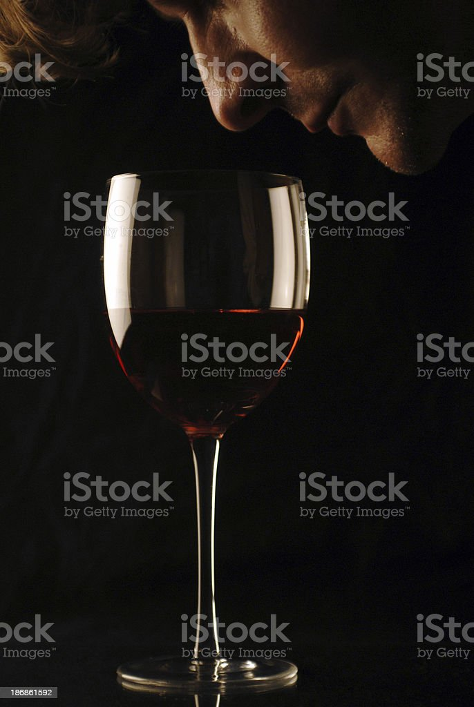 Male leaning in and about to taste wine stock photo