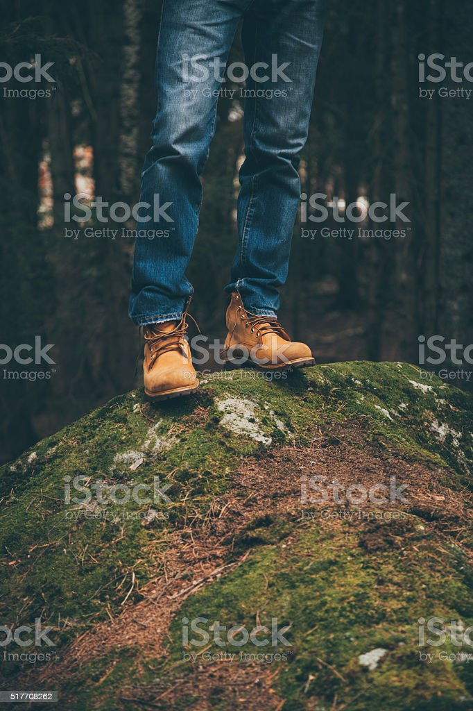 Male legs in beige leather boots, outdoors travel concept stock photo