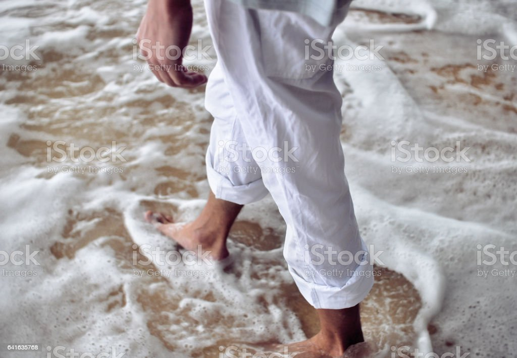 Male legs in coastal ocean foam stock photo
