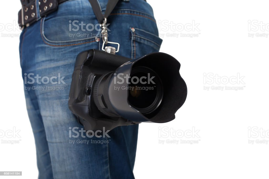 Male legs in jeans and belt holding gigital camera stock photo