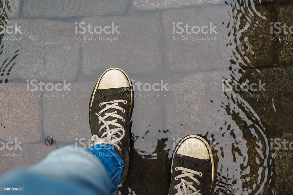 Male legs in sneakers walking through rain puddle stock photo