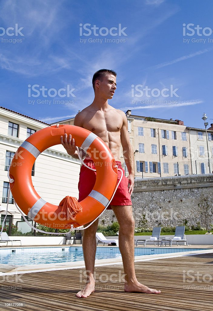 Male Lifeguard Holding Life Belt Near Swimming Pool royalty-free stock photo