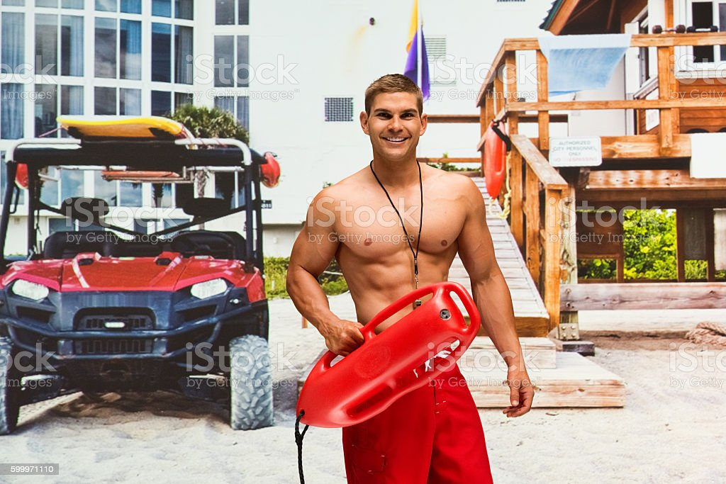 Male lifeguard holding life belt stock photo