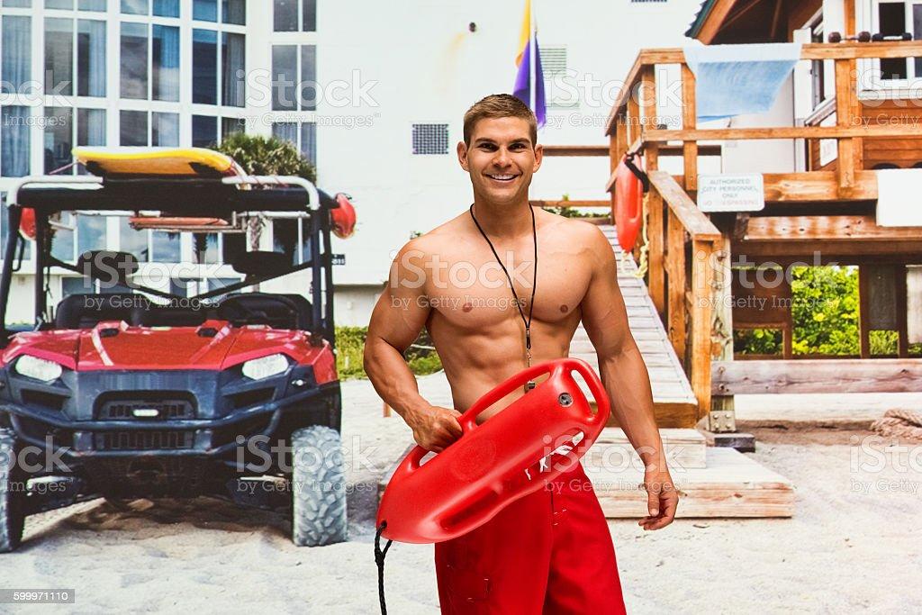 Male lifeguard holding life belt stock photo