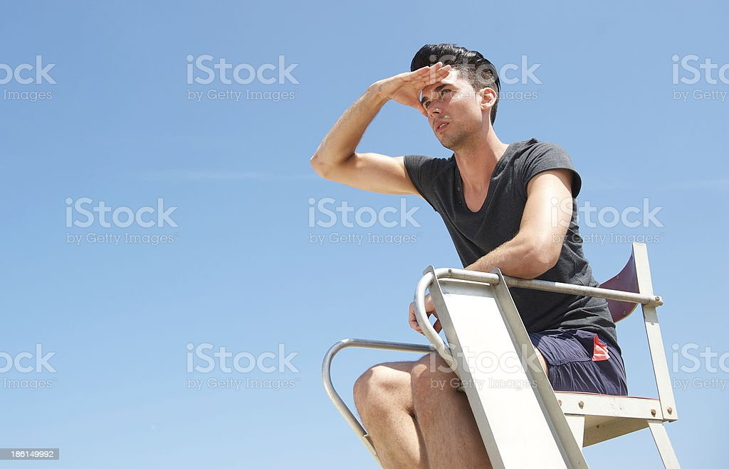 Male lifeguard looking out into the distance stock photo