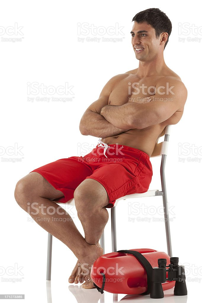 Male lifeguard sitting on a chair with his arms crossed royalty-free stock photo