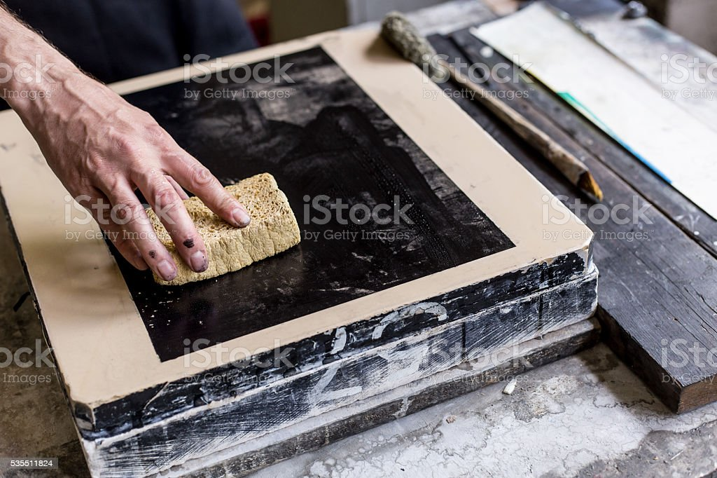 Male lithograph worker using a sponge stock photo