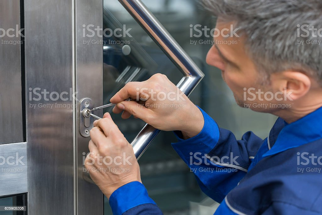 Male Lockpicker Fixing Door Handle At Home stock photo